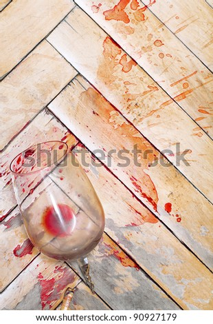 Broken wine glass on the old parquet. Splashes of wine similar to blood - stock photo