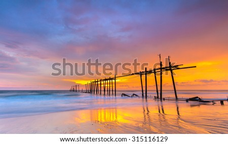 Broken wood bridge and waves crashing on sea at during sunset