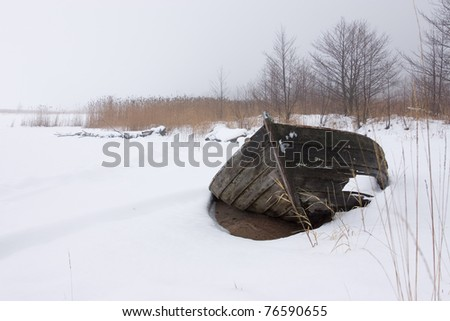 Broken wooden-boat at the beach.  (in the winter) - stock photo