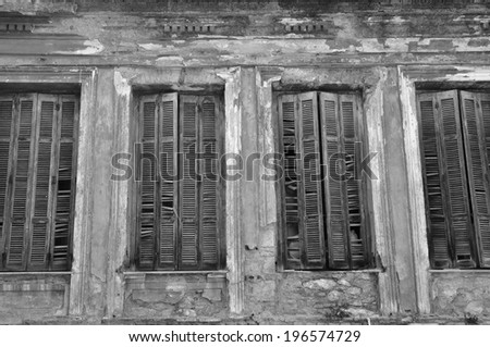 Broken wooden window shutters and textured wall of an abandoned house. Urban decay black and white. - stock photo