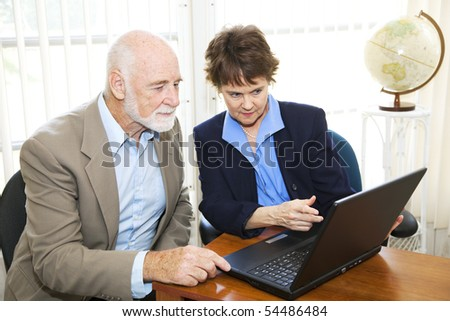 Broker and client using a computer to view his assets online.