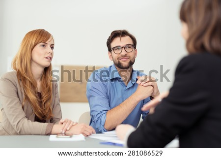 Broker having a discussion with a young couple who are sitting listening to her with serious attentive expressions - stock photo