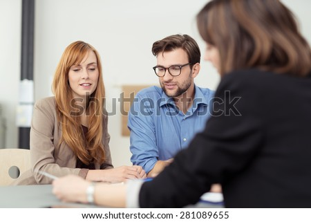 Broker making a presentation to a young couple showing them a document which they are viewing with serious expressions - stock photo