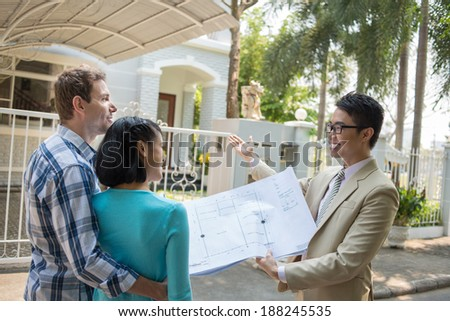 Broker showing a plan of the house to the young family - stock photo
