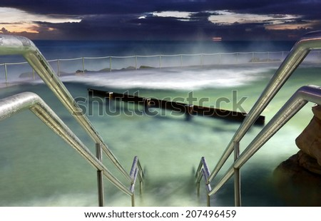Bronte Baths, ocean pool Sydney.  Waves surge into the pool constantly.  Focus is to hand rails.  Buyers this is a long 8 sec exposure taken 1 hr before sunrise at 500 iso,  there may be some grain  - stock photo