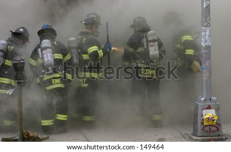 Bronx firefighters engulfed in smoke prepare to enter burning store - stock photo