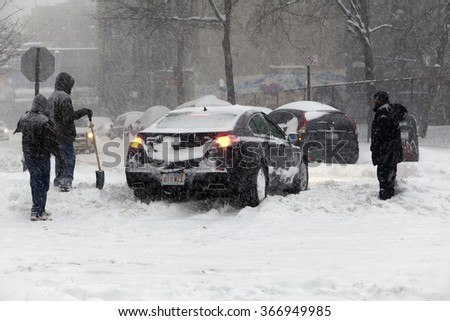 BRONX, NEW YORK - JANUARY 23: People help an auto that is stuck in snow during blizzard Jonas.  Taken January 23, 2016, in the Bronx,  New York. - stock photo