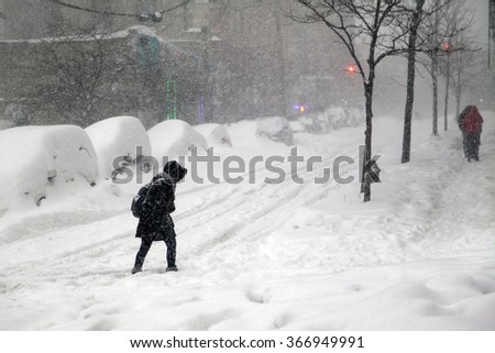 BRONX, NEW YORK - JANUARY 23: Woman crosses street during blizzard snow storm Jonas.  Taken January 23, 2016, in the Bronx,  New York. - stock photo