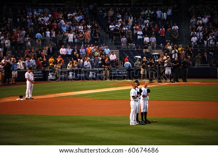 BRONX, NY - SEPTEMBER 7: Mark Teixeira, Nick Swisher, Curtis Granderson, Brett Gardner, Jorge Posada and the umpires stand at attention during the National Anthem on September 7, 2010 in Bronx, NY. - stock photo