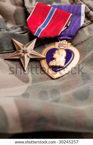Bronze and Purple Heart Medals on Camouflage Material - stock photo
