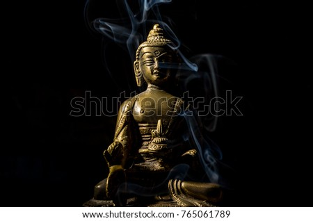 Bronze buddha in smoke isolated on black background