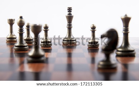 Bronze Chess Set on White Background with Wooden Chess Board, Focusing on King - stock photo