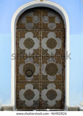 bronze church door in blue wall - stock photo