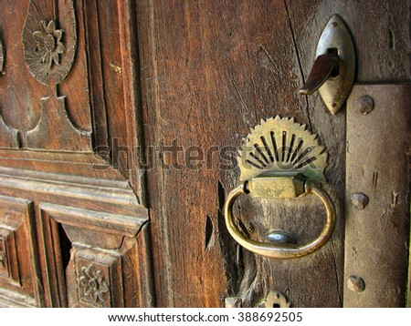 Bronze handle on an old wooden door - stock photo