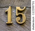 bronze house number fifteen on a stone background - stock photo