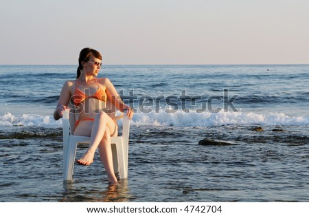 Bronze lighted girl sitting in chair sinking in sea