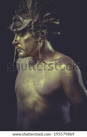 Bronze man with body painted gold feather mask and steel sword - stock photo