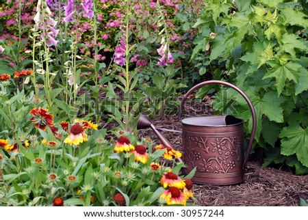 Bronze metal watering can in flower garden.  Shallow dof with focus on the can. - stock photo
