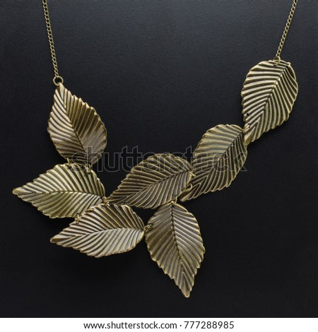 bronze necklace with leaves isolated on black