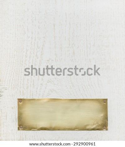 Bronze plate on white wood - stock photo