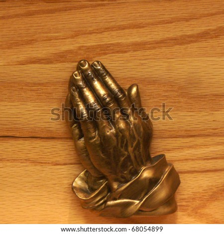 Bronze Praying Hands on Wooden Background	 - stock photo