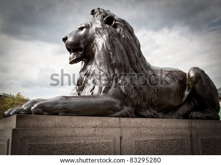 Bronze sculpture of a lion in Trafalgar Square, London on a typical british cloudy day - stock photo