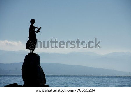 Bronze sculpture of Maiden with Seagull on background a sea and city Rijeka, Opatija, Croatia