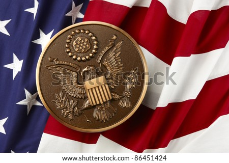 Bronze seal of the United States shot on wavy American flag - stock photo