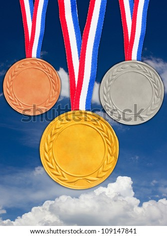 Bronze silver and golden medals with blue sky background. - stock photo