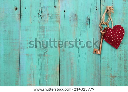 Bronze skeleton key and red heart hanging on antique teal blue weathered wood door - stock photo