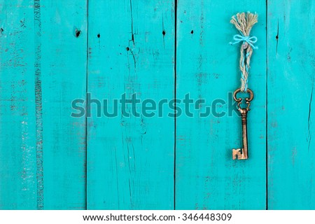 Bronze skeleton key hanging by braided rope on rustic antique teal blue wood background - stock photo