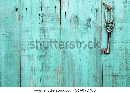 Bronze skeleton key hanging by rope on blank antique mint green rustic wood door - stock photo