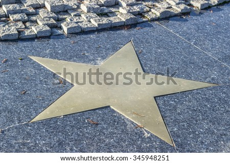 Bronze star in marble pavement Close-up horizontal view - stock photo