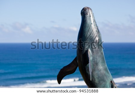 Bronze statue of whale breaching from  sea with ocean in the background