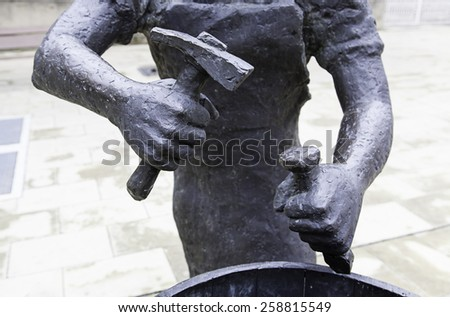 Bronze statue with a hammer, detail of a statue of a worker