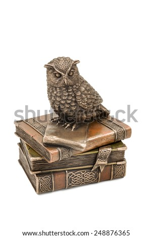 Bronze statuette owl sitting on a pile of books isolated on a white background - stock photo