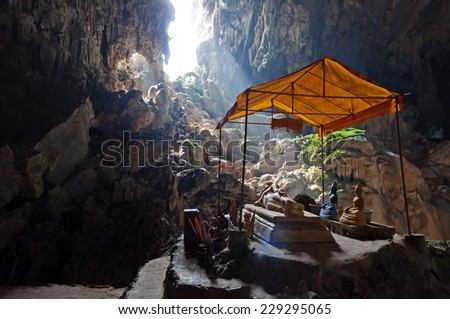 Bronze Thai Buddha in Tham Phu Kham cave near Vang Vieng. Laos. The cave is revered by the locals and contains several Buddha images - stock photo