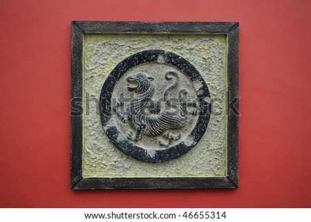 bronze tiger sculpture on a red wall - stock photo