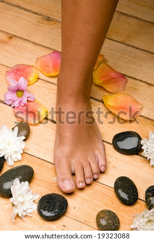 bronzed foot on sauna board floor with stones, rose-petals and flowers