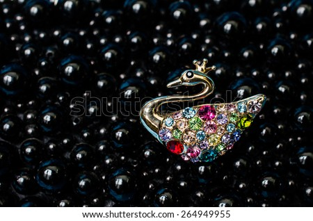 Brooch in the form of a swan on a black background - stock photo