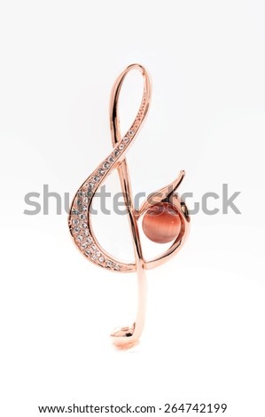 brooch in the form of a treble clef on a white background - stock photo