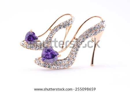 brooch in the form of shoes on a white background - stock photo