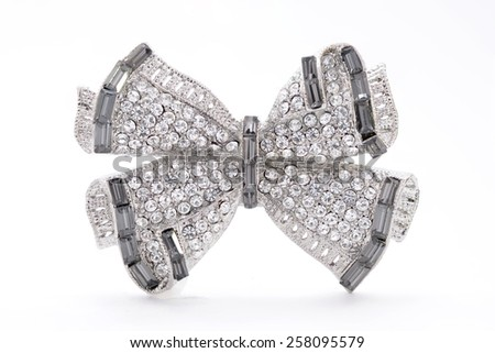 brooch in the shape of a bow on a white background - stock photo