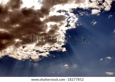 Brooding storm clouds against a blue sky with sunbeams burning through the clouds. - stock photo