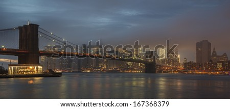 Brooklyn Bridge and New York skyline across the East River at twilight on a foggy day.