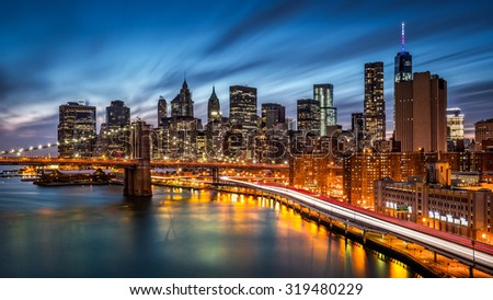 Brooklyn Bridge and the Lower Manhattan at dusk with rush hour traffic trails on FDR drive - stock photo