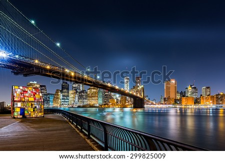 Brooklyn Bridge and the Lower Manhattan skyline by night as viewed from  Brooklyn Bridge Park in New York City - stock photo