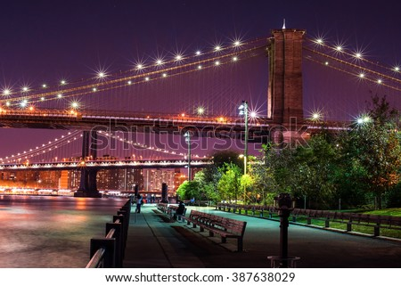 Brooklyn Bridge and the Lower Manhattan skyline by night as viewed from Brooklyn Bridge Park in New York City. - stock photo