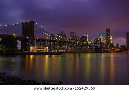 Brooklyn Bridge glowing in front of Manhattan skyline
