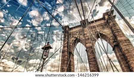 Brooklyn Bridge, New York City. Upward view with beautiful sky colors. - stock photo